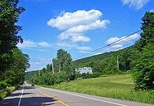 Una carretera de dos carriles bordeada de postes telefónicos atraviesa una zona boscosa rural.  Al fondo hay una cresta cubierta de árboles.