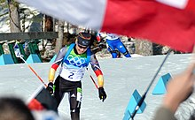 A woman in multicoloured winter sportswear which features the Olympic rings on her cheast and the number 2 in the center, moves twoards the camera. She is pictured in an area covered in snow. A second person can be seen in the background to her right. An out of focus red-and-white flag covers the upper parts of the image.