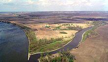 Vista della confluenza di due fiumi in una zona agricola