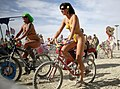 Nude cycling females at Burning man 2009.jpg