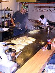 A man prepares okonomiyaki in a restaurant in Hiroshima