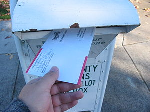 A voter returns his vote-by-mail ballot in the...