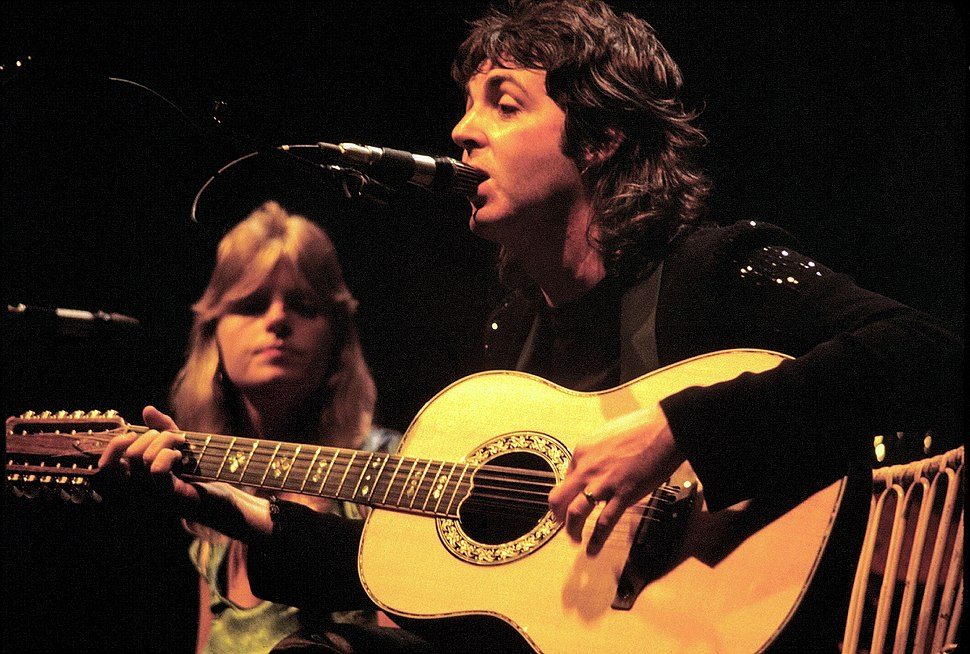 A man in the forefront is playing an acoustic guitar and singing into a microphone stand; a woman is behind microphone stand in the background.