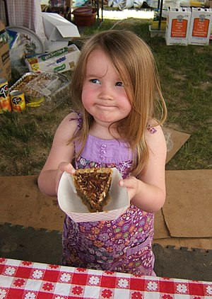 Little girl serving a pecan pie.