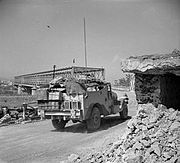 Overloaded vehicle on a road heading towards a box girder bridge. A destroyed pill box is on the right