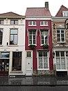 foto van Huis met eenvoudige witgepleisterde lijstgevel, segmentvormige overtoogde vensters en rood zadeldak