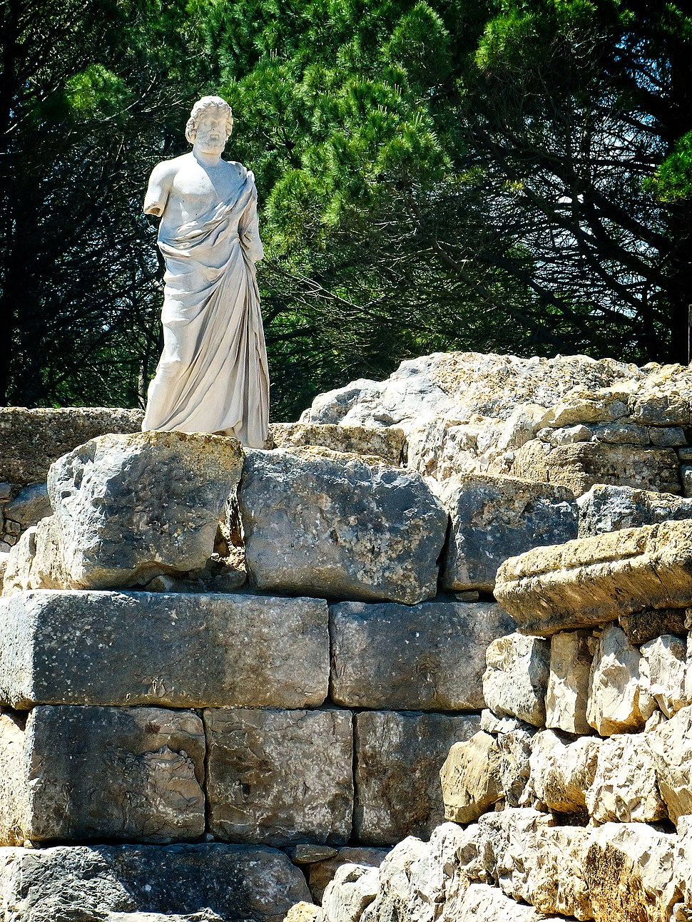 Reproduction of the statue of Aesclepius on the remains of a Greek rampart in the ancient city of Neapolis at the archaeological site of Empúries