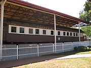 "A brown train, viewed from the side, is at rest under a small open station. ""1035 Rhodesia Railways"" is written in gold letters over the train's windows. There is a white fence and a brick walkway in front of the train."