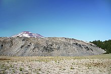 A rough-textured light-colored lava dome, with a volcanic peak behind