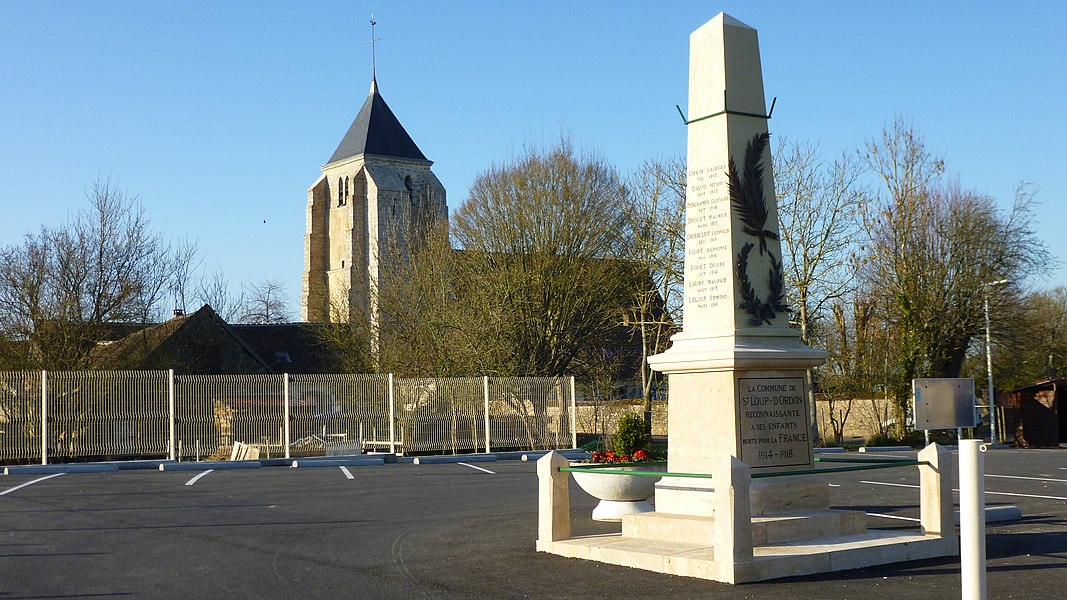 Saint-Loup-d'Ordon, Yonne, Burgundy, France.  The war monument and Saint-Loup church, seen from the front of the mairie.