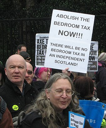 "Protesters opposing the under occupancy penalty outside the Scottish Parliament. The term ""bedroom tax"" is used by critics to describe the changes to social housing occupancy rules. Scottish Parliament. Protest March 30, 2013 - 11.jpg"