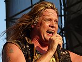 A middle-aged Caucasian man with long, blond hair and tattoos on his right shoulder wearing a sleeveless khaki shirt sings into a microphone.