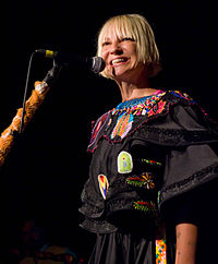 A picture of a blonde haired woman, smiling while performing