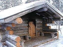سونا - ویکیپدیا، دانشنامهٔ آزادنمایی بیرونی از یک کلبه سونای دودی در فنلاند. در اوایل قرن ۱۹ میلادی، سونا به شکل کلبه ار جنس الوارهای چوبی ساخته میشد.