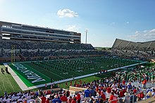 a marching band performs on the field of a football stadium