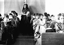 Students in the classroom, with a teacher in nun's garb at the back of the room.