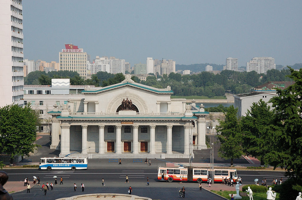 Taedongmun Cinema in Pyongyang with trolley buses passing.jpg