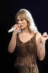 A woman performing on a microphone, wearing a sparkling dress