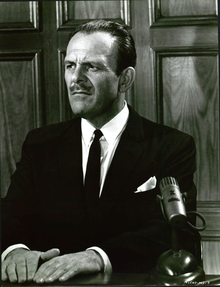 An unsmiling Terry-Thomas wearing a dark suit and tie in a witness box