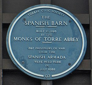 "Heritage interpretation - A ""blue plaque"" - an example of a concise interpretive sign. This plaque provides information about The Spanish Barn at Torre Abbey in Torquay, England."