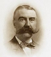 Black-and-white portrait of a white man with a large mustache