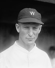 "A wearing a white baseball jersey with a dark cap with a white ""W"" on the center."