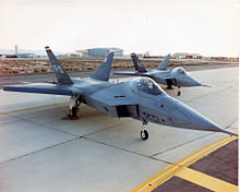 Two jet aircraft with outward-canted vertical stabilizers parked on an angle on ramp.