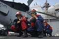 U.S. Navy Damage Controlman 1st Class Peter Martinez, right foreground, instructs Hull Maintenance Technician Fireman Michael Johnson, left, on proper hose handling techniques during a crash and salvage drill 110730-N-DU438-073.jpg