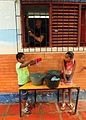U.S. Navy Lt. Lance Ruth, center, assigned to guided missile frigate USS Klakring (FFG 42), paints window shutters as children clean paint rags during a joint community relations project with the Colombian navy 100821-N-HI707-749.jpg