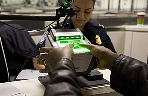 Office of Biometric Identity Management - A person using a US-VISIT scanner