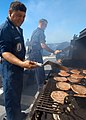 US Navy 040920-N-3019M-006 Boatswain's Mate 1st Class Jesse Rodriguez cooks hamburgers, hot dogs and chicken for family members.jpg
