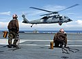 US Navy 050111-N-6817C-110 Line Division personnel prepare to chock and chain an MH-60S Knighthawk helicopter prior to landing on the flight deck aboard USS Abraham Lincoln (CVN 72).jpg