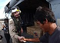 US Navy 050113-N-4451V-099 Cmdr. Daryl R. Hancock, assigned to Bonhomme Richard (LHD 6) Expeditionary Strike Group, shakes an Indonesian man's hand after distributing water and rice from an MH-60S Knighthawk helicopter.jpg