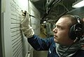 US Navy 061019-N-3143M-010 Aviation Electronics Technician 3rd Class Brian Clark fills out charts while operating a sound powered telephone during a general quarters drill aboard USS Harry S. Truman (CVN 75).jpg