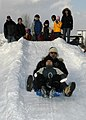 US Navy 070208-N-4649C-125 Ship's Serviceman 2nd Class Harlig Medina slides down a snow slide as others look on at the Kosho Gakuen Home for Children in Sapporo, Japan.jpg
