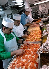 US Navy 070406-N-2959L-756 Members of USS Ronald Reagan (CVN 76) First Class Association prepare and put toppings on pizzas in the galley as part of a special dinner prepared for the crew