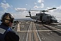 US Navy 071205-N-9123L-001 A Sailor aboard the guided missile destroyer USS McCampbell (DDG 85) stands by as a SH-60B helicopter prepares to lift off.jpg