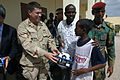 US Navy 071215-N-3931M-054 Capt. Dennis Gallagher from Combined Joint Task Force-Horn of Africa (CJTF-HOA) presents a gift to a local student at a school dedication ceremony in Ali Adde.jpg