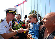US Navy 080824-N-4044H-059 Capt. John Moore, commodore, Combined Task Force (CTF) 367, greets local residents and receives flowers shortly after the arrival of the guided-missile destroyer USS McFaul (DDG 74) to the port of Bat