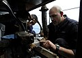 US Navy 091104-N-7280V-772 Chief Engineman Manuel Jamosmos, left, and Engineman Fireman Kelly Cunningham replace a gasket on a slewing arm davit pump motor aboard the amphibious command ship USS Blue Ridge (LCC 19).jpg