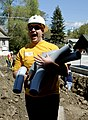 US Navy 100512-N-4929M-097 Machinist's Mate 1st Class Bennie J. Cooley moves conduit piping on the job site of a Habitat for Humanity building project.jpg
