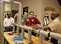 US Navy 100715-N-5096L-026 Machinist's Mate 1st Class Derrick Edwards explains various pipe patching methods to a group of educators during an educator orientation visit.jpg