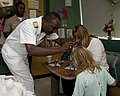 US Navy 100811-N-2389S-058 Rear Adm. Kenneth Carodine gives a Navy necklace to a patient at a children's hospital as part of Caps for Kids during Chicago Navy Week.jpg
