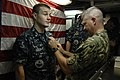 US Navy 100830-N-9818V-626 Master Chief Petty Officer of the Navy (MCPON) Rick West pins the Enlisted Submarine Warfare pin on Electronics Technician 3rd Class Derrick Zulick.jpg
