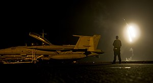 US Navy 120101-N-TZ650-042 A Sailor observes celebratory flares shot to mark the new year on the flight deck aboard the Nimitz-class aircraft carri.jpg