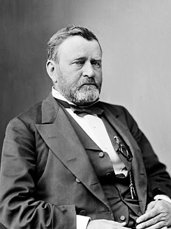 Ulysses S. Grant in a formal black and white photo. Grant is seated with arms folded. Grant looks weary and his beard is greying. This is the photo used for the $50.00 bill.