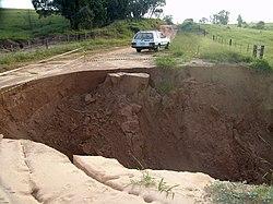 Erosão tomando parte de estrada rural