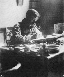 Black-and-white photograph of a man with a large mustache and a pipe in his mouth, at work, seated behind a cluttered desk on which a drawing board is propped at a slight angle.