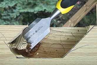 Chisel - A sharp wood chisel in combination with a forstner wood drill bit is used to form this mortise for a half-lap joint in a timber frame.