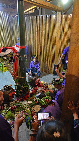 Taivoan people - Taivoan men worshiping the ancestral spirits inside the Shrine at the Night Ceremony. A bamboo basket fastened to the central axial column can be seen.